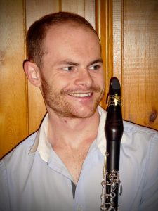 Full to side profile shot of Christopher Gibbons and bottom end of clarinet. Chris wears a white shirt.